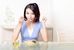 La verticale de la jeune femme de sourire heureuse mangent de la salade Image libre de droits