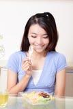 La verticale de la jeune femme de sourire heureuse mangent de la salade Images libres de droits