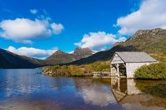 La vertiente hermosa de la montaña y del barco de la cuna del paisaje en el lago se zambulló imagen de archivo