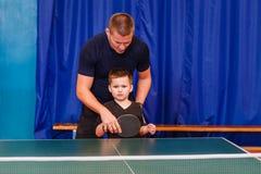 La vettura insegna al bambino a giocare il ping-pong fotografia stock