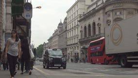 La via dalla città della città di Londra con le automobili traffica i bus ed il taxi rossi video d archivio