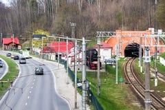 La via della città con la linea del filobus ed automobili e ferrovia recinta il goin Immagini Stock