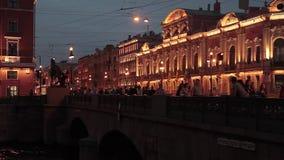 La via della città di notte, la gente supera il ponte archivi video