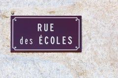 La via delle scuole firma su una parete in francese Immagini Stock