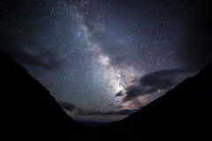 La Via Lattea illumina le nuvole nelle montagne Plateau Kara- immagini stock