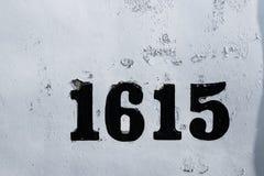 La via numera 1615 su pittura indossata sbiadita scheggiata bianco immagini stock libere da diritti