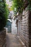 La via stretta nella fortezza di pietra con le lanterne Fotografia Stock