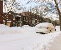 La via urbana dell'inverno con le automobili ha attaccato in neve fotografia stock libera da diritti