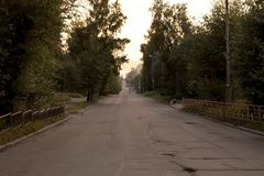 La via vuota alla notte con la cattiva strada asfaltata rurale immagini stock
