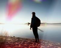 La viandante alta in abiti sportivi scuri con i pali e lo zaino sportivo camminano sulla spiaggia Il turista gode dell'alba Fotografie Stock Libere da Diritti