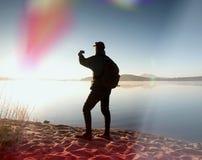 La viandante alta in abiti sportivi scuri con i pali e lo zaino sportivo camminano sulla spiaggia Il turista gode dell'alba Fotografie Stock