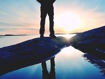 La viandante alta in abiti sportivi scuri con lo zaino sta sulla scogliera sopra il mare L'uomo gode del tramonto stupefacente Fotografia Stock Libera da Diritti
