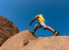 La viandante che salta sopra la roccia Immagini Stock