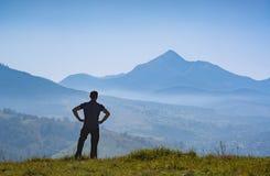 La viandante che sta su una collina e gode della cresta dell'alta montagna Immagini Stock