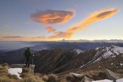 La viandante con backpacking osserva le alpi Fotografia Stock