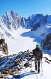 La viandante con gli zainhi raggiunge la sommità del picco di montagna Succes Immagine Stock Libera da Diritti