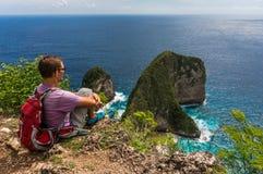 La viandante con lo zaino che si siede sulla cima della montagna e gode della vista Immagine Stock