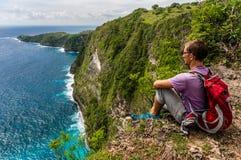 La viandante con lo zaino che si siede sulla cima della montagna e gode della vista Fotografie Stock