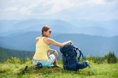 La viandante della donna che fa un'escursione sulla collina erbosa, zaino d'uso, facendo uso del trekking attacca nelle montagne fotografia stock libera da diritti