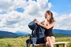 La viandante della donna che fa un'escursione sulla collina erbosa, zaino d'uso, facendo uso del trekking attacca nelle montagne immagini stock libere da diritti