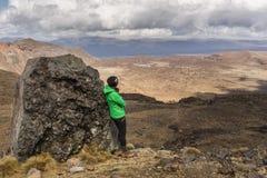 La viandante della donna che pende contro la roccia vulcanica e gode della vista Fotografia Stock Libera da Diritti