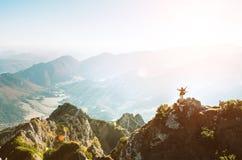 La viandante della montagna con la figurina minuscola dello zaino sta sul supporto più hiest fotografia stock
