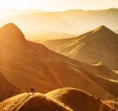 La viandante della ragazza contempla la valle della montagna fotografia stock