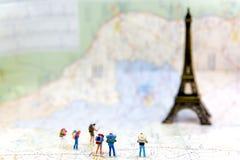 La viandante ed il viaggiatore miniatura del gruppo backpack la condizione sulla mappa del wold per la torre Eiffel di viaggio in immagini stock