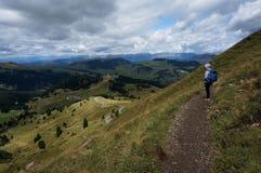 La viandante gode della vista ove alp de siuisi sotto le nuvole drammatiche Immagini Stock Libere da Diritti