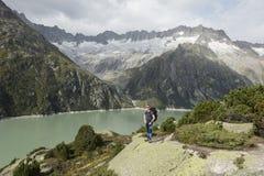 La viandante gode della vista strabiliante di un lago della montagna Fotografie Stock Libere da Diritti
