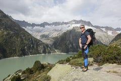 La viandante gode della vista strabiliante di un lago della montagna Immagine Stock
