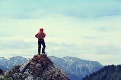 la viandante gode della vista sulla scogliera della cima della montagna Fotografie Stock
