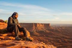 La viandante incontra il tramonto al grande punto di vista in Canyonlands p nazionale Immagine Stock