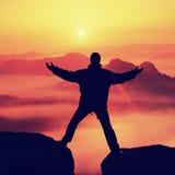 La viandante nel nero celebra il trionfo fra due picchi rocciosi Alba meravigliosa in montagne rocciose, foschia arancio pesante  Fotografie Stock