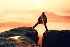 La viandante nel nero sta saltando fra i picchi rocciosi Alba meravigliosa in montagne rocciose, foschia arancio pesante in valle Immagini Stock
