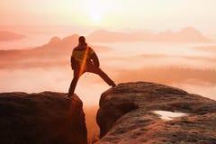 La viandante nel nero sta saltando fra i picchi rocciosi Alba meravigliosa in montagne rocciose, foschia arancio pesante in valle Immagini Stock Libere da Diritti