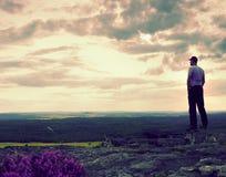 La viandante o lo sportivo alta sulla scogliera in montagne rocciose parcheggia e guarda giù paesaggio Fotografie Stock