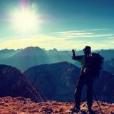 La viandante prende la foto del telefono Equipaggi sul picco di montagna delle alpi Vista alla valle nebbiosa blu Fotografia Stock Libera da Diritti