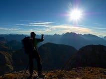La viandante prende la foto del telefono Equipaggi sul picco di montagna delle alpi Vista alla valle nebbiosa blu Immagine Stock