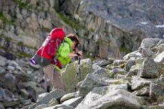 La viandante sta scalando il pendio roccioso della montagna in montagne di Altai, Ru Fotografia Stock Libera da Diritti