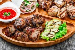 La viande et les légumes grillés délicieux assortis avec de la salade et le BBQ frais sauce sur la planche à découper sur le fond Photos libres de droits