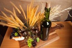 La vid de uva con el vidrio y la hierba florecen en la tabla de madera Imagen de archivo libre de regalías