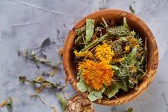 La vida del balneario todavía con las flores en cuenco de madera en luz texturizó el fondo, visión superior, primer, foco selecti Imagenes de archivo