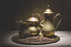 La vida del vintage todavía con el montón de los granos de café acerca a las cafeteras de cobre viejas en la bandeja de bronce co Imagen de archivo