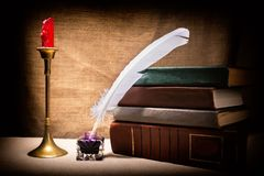 La vida del vintage todavía con los libros viejos acerca al inkstand, a la pluma y a la vela en palmatoria en fondo de la lona Co Fotografía de archivo libre de regalías