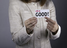 ¡La vida es buena! Empresaria que sostiene una tarjeta con un texto de mensaje w Imagenes de archivo