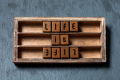 La vida es vida, enfrente del concepto opuesto La caja de madera lamentable, cubos con las letras del viejo estilo, piedra gris t fotos de archivo libres de regalías