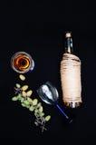 La vida inmóvil con el vino blanco en la botella de cristal en fondo negro Vidrios de vino con las uvas frescas Botella y vidrio  Imagenes de archivo