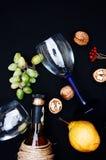 La vida inmóvil con el vino blanco en la botella de cristal en fondo negro Vidrios de vino con las uvas frescas Botella y vidrio  Foto de archivo libre de regalías