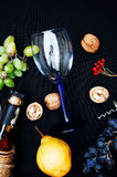 La vida inmóvil con el vino blanco en la botella de cristal en fondo negro Vidrios de vino con las uvas frescas Botella y vidrio  Foto de archivo